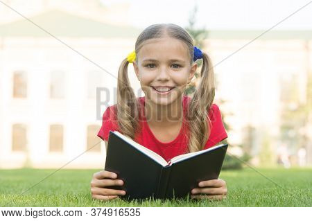 Open Your Imagination, Read. Happy Kid Read Book On Green Grass. Developing Imagination. Childhood I