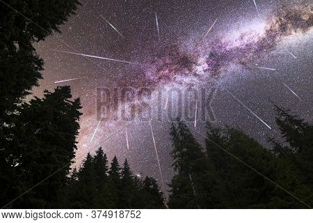 A View Of A Meteor Shower And The Purple Milky Way With Pine Trees Forest Silhouette In The Foregrou