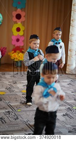 Portrait Of Cute Funny Boys In White Shirt And Blue Neckerchief And Forage-cap In Kindergarten