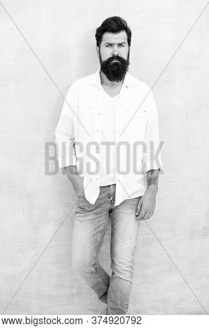 Fashion Portrait Of Young Bearded Man. Hipster Guy Wear Jeans And Shirt. Brutal Bearded Man With Tat