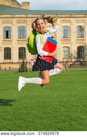 Cute Girl Jump With Notebook. Happy Preschool Girl With Book In School Yard. Back To School. Hardwor