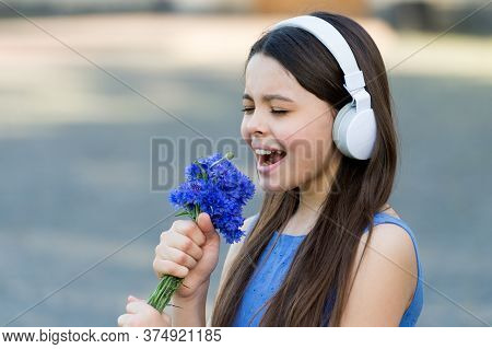 Kiddie Song. Happy Kid Sing Song Outdoors. Using Flowers As Microphone. Little Child Enjoy Singing I