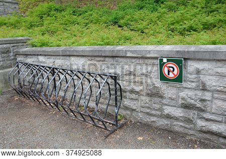 No Parking Sign With Metal Bike Rack And Stone Wall