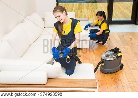 Professional Cleaning Service. Two Women In Working Uniform, In Aprons. Two Women In Working Uniform