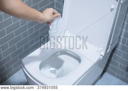 Woman Hand Throw Paper Towels In The Toilet Bowl. Cleaning, Lifestyle And Personal Hygiene Concept