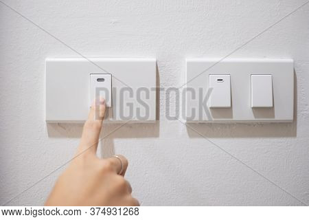 Female Finger Is Turn On Or Off On Light Switch On White Wall At Home. Energy Saving, Power, Electri