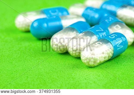 Blue Gelatin Capsules With White Granules Inside, Isolated On A Green Background, Macro Shot.
