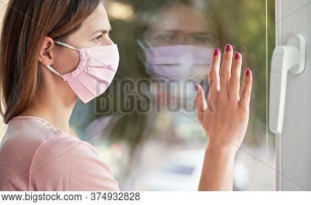 Young Woman In Virus Mask Looking Sad From The Window Behind Glass Pane, Touching It With Hand. Quar