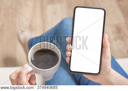 Mockup Image Of Woman Holding Black Mobile Phone With Blank White Screen In Cafe. Cropped Shot View
