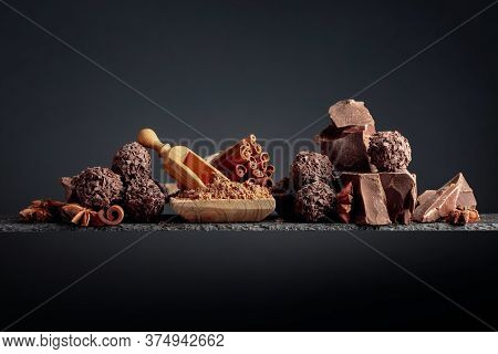Chocolate Truffles With Broken Pieces Of Chocolate. Chocolate, Cinnamon Sticks And Anise On A Dark B