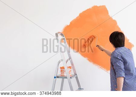 Renovation, Redecoration And Repair Concept - Middle-aged Woman Painting Wall In New Home. Copy Spac