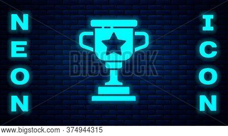 Glowing Neon Award Cup Icon Isolated On Brick Wall Background. Winner Trophy Symbol. Championship Or