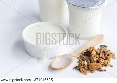 Healthy Flavored Yogurt In Plastic Cup And Ceramic Bowl With Granola On White Background For Organic