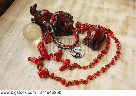 Composition Of A Crimson Horse Figurine, Red Beads Made Of Natural Coral, A Bracelet With A Yin Yang