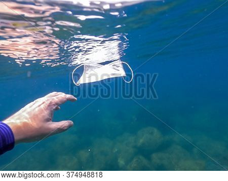 Man Hand Picking Up Discarded Used Disposable Medical Mask Floats In Sea Waters