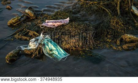 Coronavirus Polluting Environment. Waves Wash Up Old Medical Mask Waste