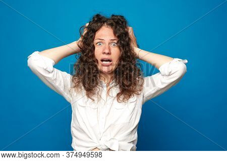 Indoor Portrait Of Desperate Annoyed Female Screaming In Rage And Anger, Tearing Hair Out While Feel