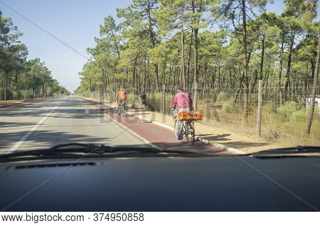 Driving Slowly Behind Two Cyclists At Forest Road. View From The Inside Of The Car