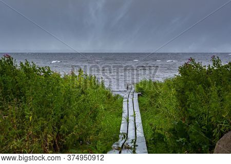 A Boardwalk With The Blue Ocean In The Background. Dark Dramatic Clouds. The Picture Was Taken Near