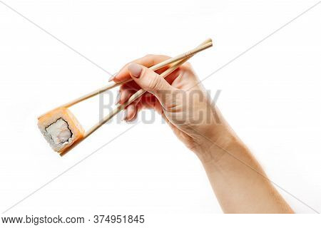 A Female Hand Holds A Roll Of Chopsticks. Isolated On White Background Hand With Chopsticks And Roll