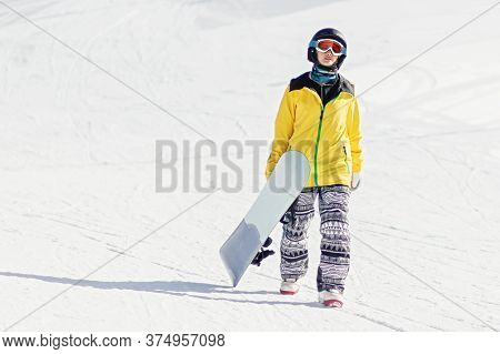 Young Woman Snowboarder Walking On Ski Slope Holding Her Snowboard, Shes Looking At Camera, Copy Spa