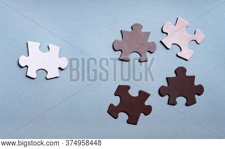 Colored Jigsaw Puzzle Pieces On Gray Background Top View. Concept For Unite To End Racism. Symbol Of