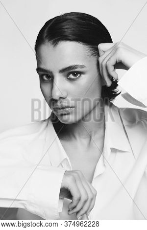 Vintage style black and white portrait of young beautiful tomboy with painted moustache