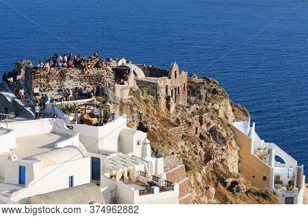 Oia, Santorini, Greece, July 17 2010: Tourist People At The Roof Of A Traditional House Waiting For