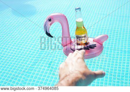 Kharkiv, Ukraine - 26 June, 2020: Illustrative Editorial Of Corona Beer In The Pool. Hand Wants To T