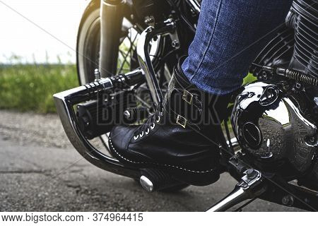 A Woman's Leg In Leather Boot Stands On The Pedal Of A Motorcycle
