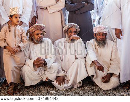 Nizwa, Oman, December 2, 2016: Local men shopping at the Friday goat market in Nizwa, Oman