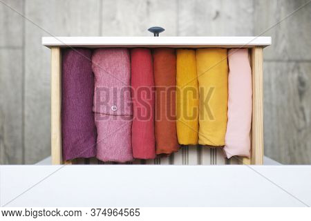 Women's Clothing Neatly Folded.in A Drawer Of A Pink And Yellow Dressers Folded In The Dresser
