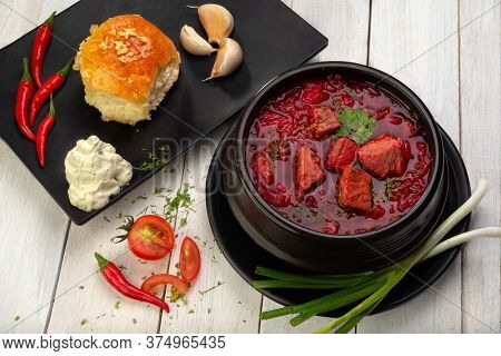 Traditional Ukrainian Russian borscht or red soup in the bowl. Tasty beetroot soup in bowl. Traditional ukrainian, russian soup (borscht) with sour cream and garlic donut on a light wooden table.