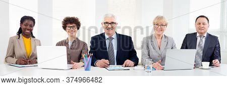 Multy-ethnic group of young business people working while sitting at the office desk and smiling at camera