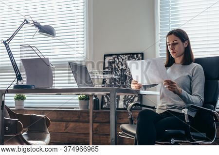 Woman Works With A Document Sitting At Her Desk
