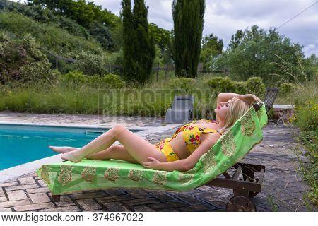Sexy blonde woman in yellow bikini posing at the poolside