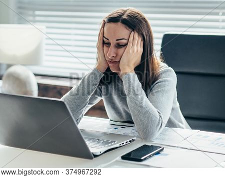 Woman Sitting At Table With Her Head Leaning On Her Hands And Looking At Laptop Monitor.