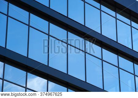 facade of a modern building on a bright Sunny day, blue sky and clouds reflecting in a glass, beautiful exterior of the new building