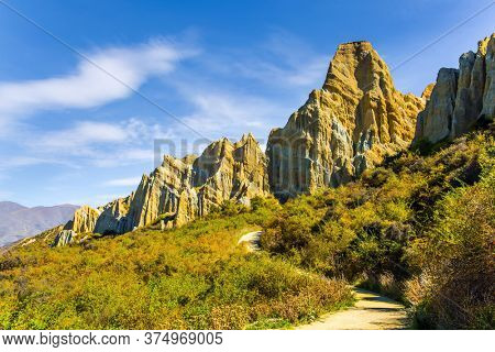 New Zealand, South Island. Dirt path passes around majestic clay cliffs. Ridges of the Clay Cliffs separated by narrow ravines. The concept of exotic, extreme, natural and photo tourism