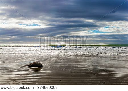 Moeraki's huge round boulder on a sandy beach. The Pacific ocean tide begins. New Zealand. The sun's rays are reflected in the ocean water. Noon. The concept of ecological, photo and exotic tourism