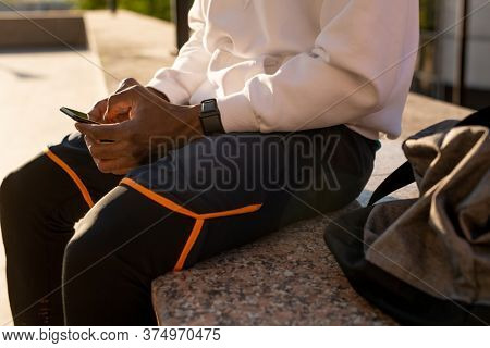 Hands of young African man with smartphone surfing through online news while sitting on marble tile and having rest after outdoor training