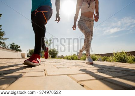 Low section of two young active intercultural runners in sportswear jogging down brick pavement or road on sunny summer morning