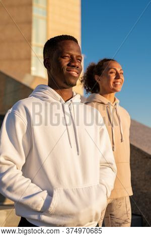 Happy young African sportsman and his girlfriend of Caucasian ethnicity in hoodies standing against modern architecture and blue sky