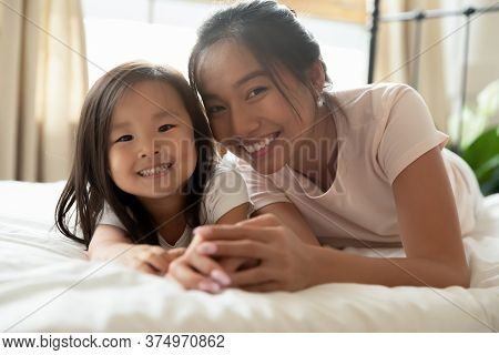 Adorable Small Vietnamese Baby Lying On Bed With Mommy.
