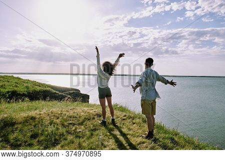 Rear view of young ecstatic couple in casualwear standing on green grass on riverbank and enjoying sunny weekend by seaside