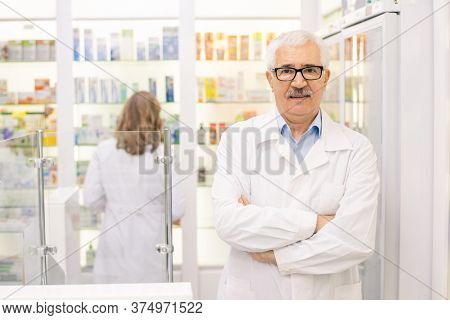 Contemporary senior expert in pharmacy and medicine standing against large display with healthcare goods and looking at you