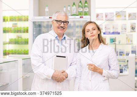 Pretty blond female pharmacist and her senior colleague in whitecoats standing in front of camera against large displays with medicine