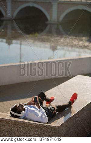 Young relaxed African man in sportswear and white headphones lying by riverside after outdoor training and enjoying rest with music
