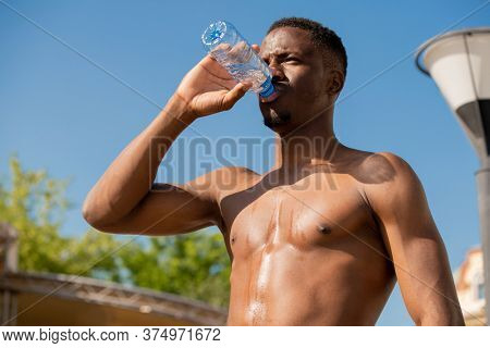 Young shirtless thirsty sportsman drinking water from bottle while standing against blue sky and green foliage after hard training