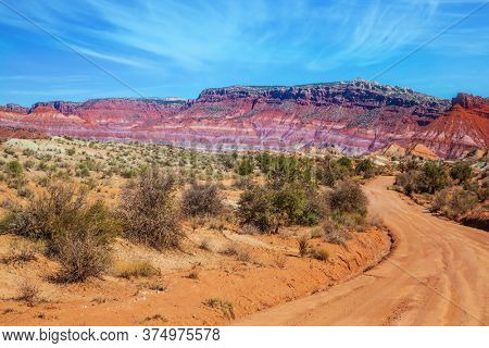 Red sandstone dirt road. Huge slopes of red sandstone, striped from various inclusions of light rocks. Paria Canyon-Vermilion Cliffs Wilderness Area. The concept of extreme and photo tourism